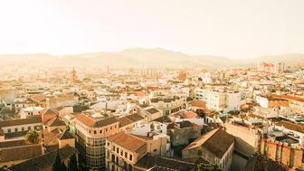 A beautiful bird's eye view of the Barcelona, Spain city skyline at sunrise showcasing the architecture.