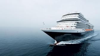 The Holland America Koningsdam ship sailing through fog on the open seas.