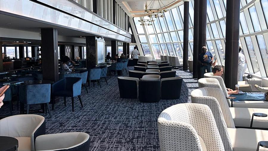 A view of the Observation Lounge onboard Norwegian Joy that features panoramic aft views and lounge chairs.