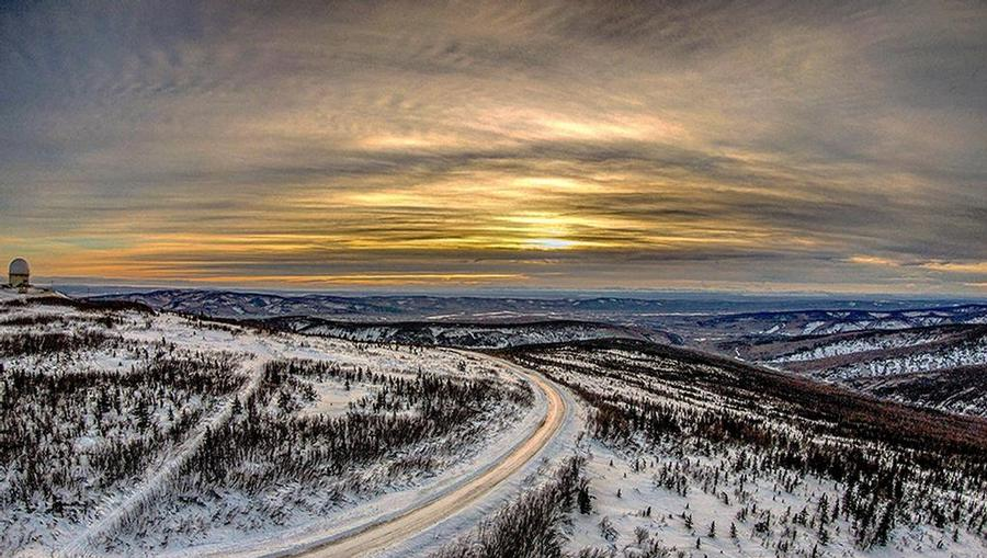 The sun rising over a winding road and white snow-covered hills in Fairbanks, Alaska.