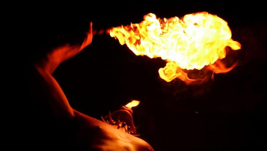 An artistic photo of a traditional Polynesian dancer blowing flames at a Luau in Maui.
