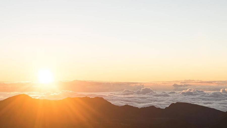 The sun rising over Haleakala National Park, with rays of sunlight shining through clouds over a beautiful mountain scape.