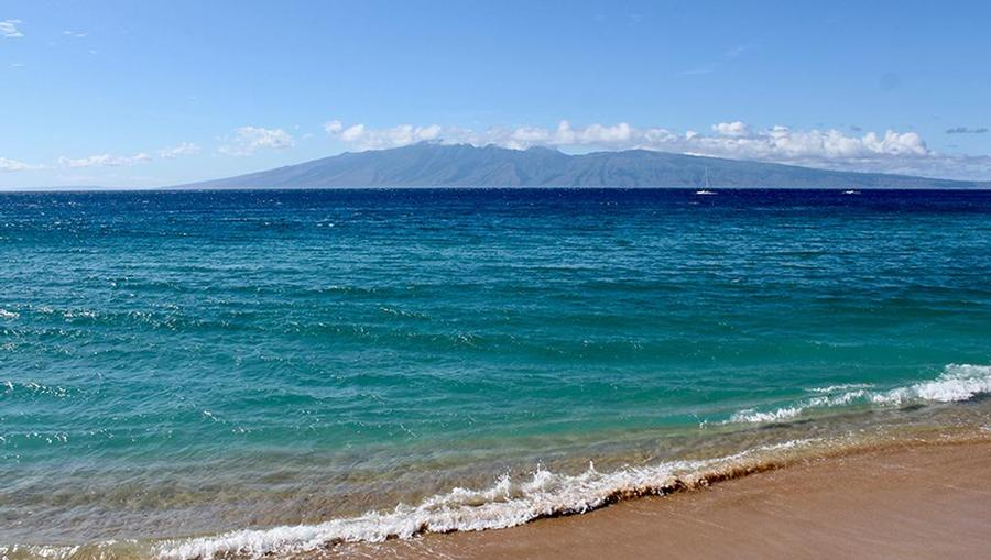 Bright and vibrant blue waters washing up on the shore of Kaanapali Beach in Maui.